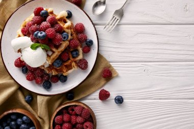 top view of freshly baked belgian waffles with berries and ice cream on white wooden table