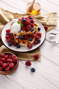 freshly baked belgian waffles with berries on white wooden table