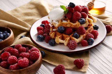 fresh belgian waffles with berries and ice cream on white wooden table