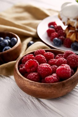 close-up shot of bowls with berries with belgian waffles blurred on background on white wooden table