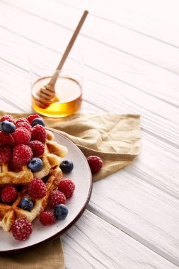 tasty belgian waffles with berries and glass of honey on white wooden table