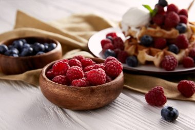bowls with berries with belgian waffles blurred on background on white wooden table