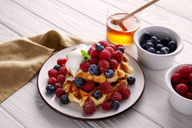tasty belgian waffles with berries and ice cream on white wooden table