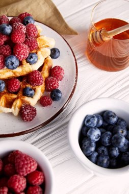 close-up shot of delicious belgian waffles with berries and honey on white wooden table