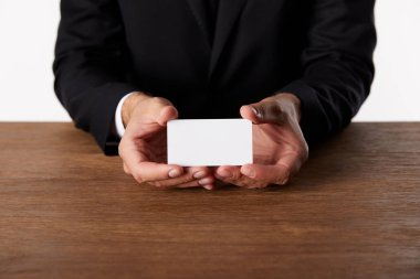 cropped image of businessman showing empty business card at wooden table