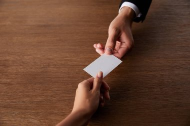 cropped image of businessman giving empty visit card to businesswoman at wooden table