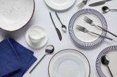 top view of different ceramic plates, cup, kitchen towel, forks, spoons and knife on white table