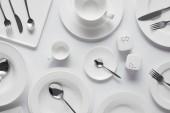 Fotografie Draufsicht der Löffel, Gabeln, Messer, verschiedene Teller, Schüssel, Salzstreuer, Pfeffer Caster und Tasse auf weißen Tisch