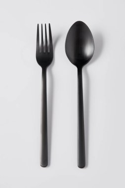 top view of black fork and spoon on white background, minimalistic concept