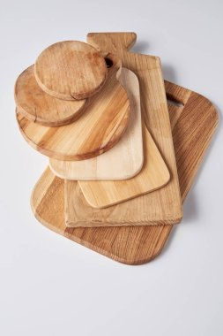 High angle view of stack of different wooden cutting boards on white table stock vector