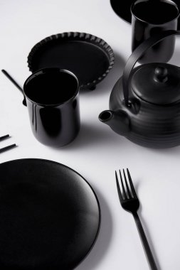 close up view of black teapot, plate, cups, fork, chopsticks and baking dish on white table