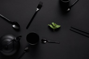 Top view of black teapot, chopsticks, various spoons, fork, cup and mint leaves on black table