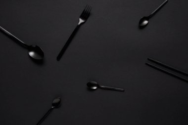 top view of black various spoons, fork and chopsticks on black table