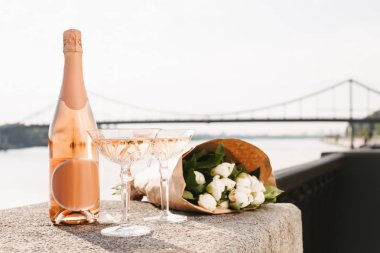 beautiful bouquet of flowers, glasses and bottle of champagne near river at sunset