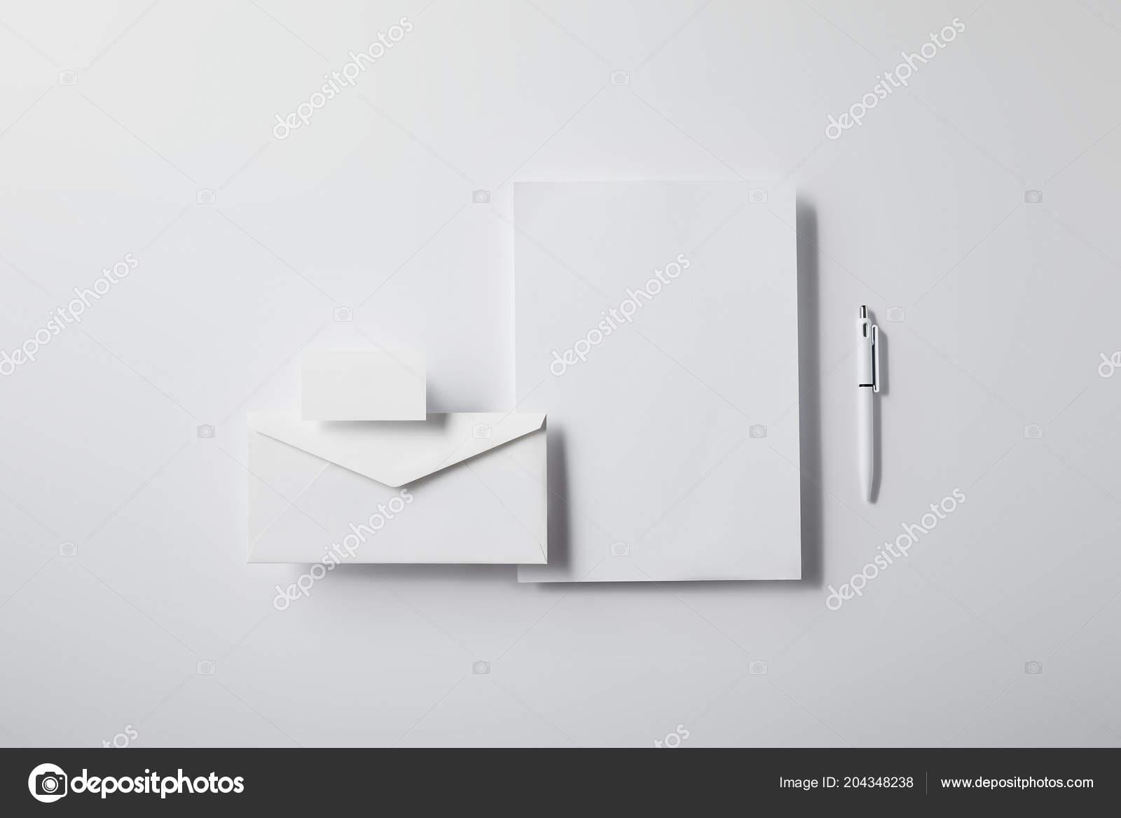 Top view arranged envelope pen blank paper business card white top view of arranged envelope with pen blank paper and business card on white tabletop for mockup foto de antonmatyukha reheart Gallery