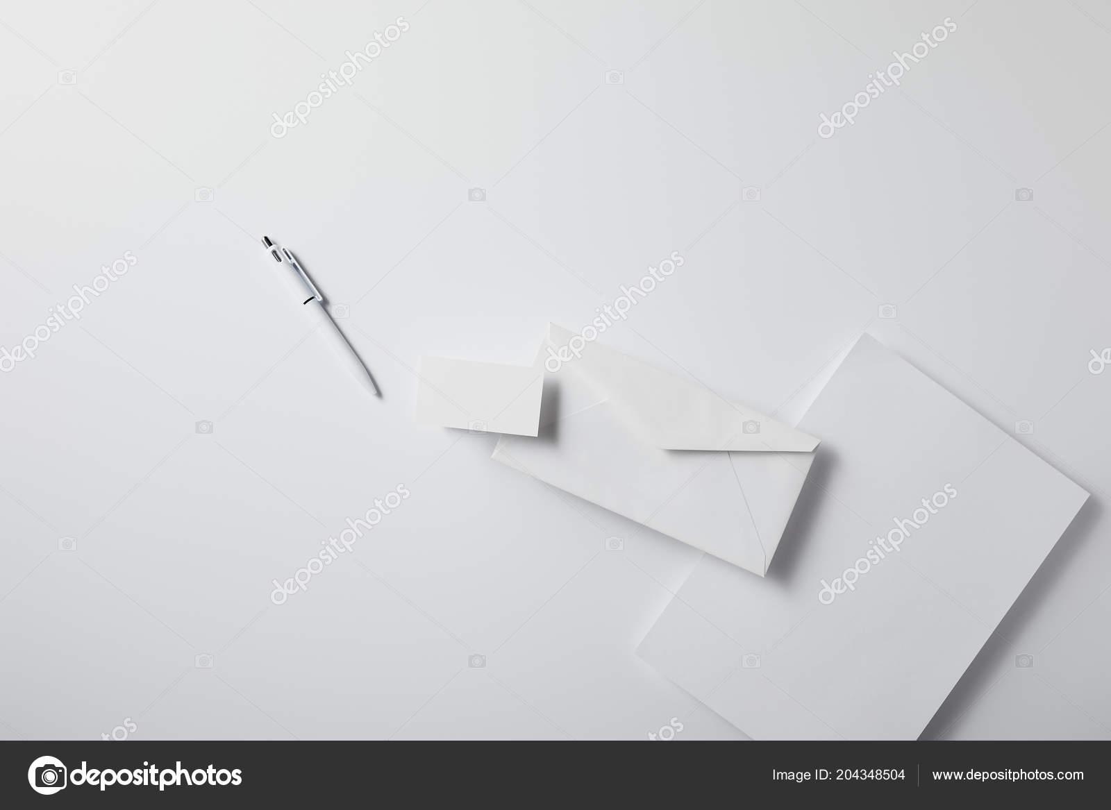 Top view arranged envelope pen blank paper business card white top view of arranged envelope with pen blank paper and business card on white surface for mockup fotografia por antonmatyukha reheart Gallery
