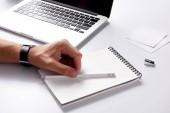 Fotografie Oříznout záběr člověka s Poznámkový blok a tužka ležící na pracovišti na bílý povrch