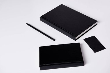 Close-up shot of black notebooks  on white surface for mockup stock vector