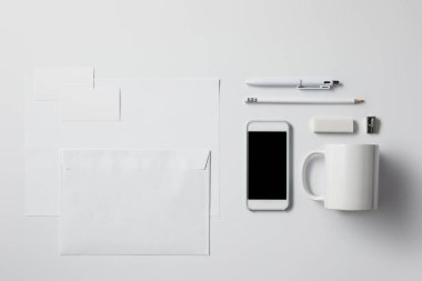 top view of smartphone with various supplies and blank papers on white surface for mockup