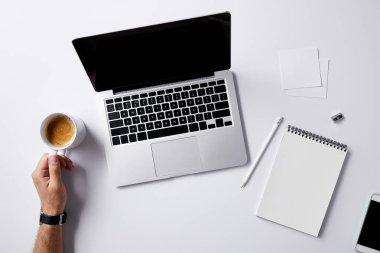 cropped shot of man folding coffee cup at workplace with supplies on white surface for mockup