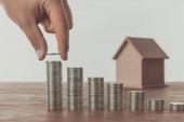 Photo cropped image of man stacking coins near small house on table, saving concept