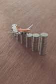 toy plane on stacks of coins on wooden tabletop, saving concept