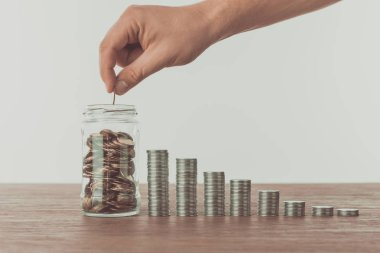 cropped image of man putting coin into jar on wooden table, saving concept