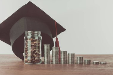 stacks of coins, jar with coins and graduation cap on wooden table, saving concept