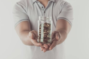 cropped image of man showing jar of coins in hands isolated on white, saving concept