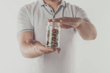 cropped image of man holding jar of coins in hands isolated on white, saving concept