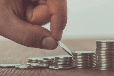 cropped image of man stacking coins on wooden table, saving concept