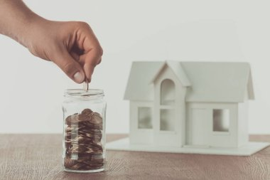 cropped image of man putting coin into glass jar with small house on table, saving concept