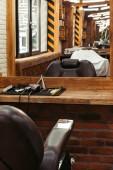 moderní holičství interiér odráží v zrcadle a profesionální kadeřnictví nástroje na dřevěné police