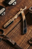 close-up view of straight razor and scissors on wooden surface in barbershop