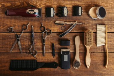 top view of professional hairdressing equipment on wooden table in barbershop