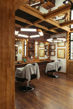 empty chairs and mirrors in modern barbershop