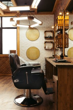 empty chair, mirrors and lamps in modern barbershop interior