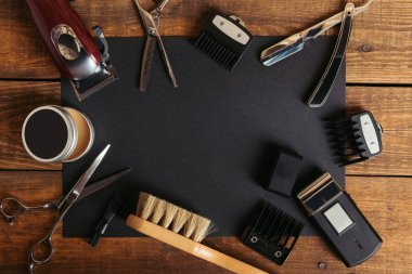 top view of various professional barber tools on black card on wooden surface