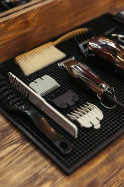 close-up view of various professional barber tools on wooden shelf in barbershop