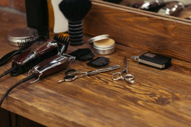 close-up view of various barber tools on wooden shelf in barbershop