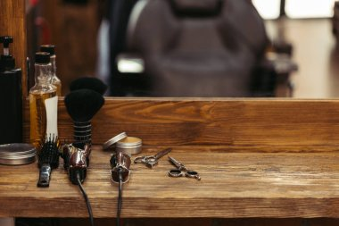 barber tools on wooden shelf and mirror in barbershop
