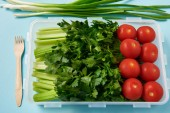 Photo close up view of fork and food container full of fresh tomatoes, parsley and celery on blue background
