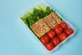 close up view of food container full of healthy vegetables and cookies with seeds on blue backdrop
