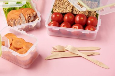 close up view of healthy food arranged in food containers and cutlery on pink backdrop