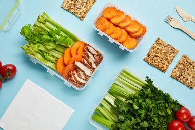 top view of arrangement of food containers with fresh healthy food, napkin and cutlery isolated on blue