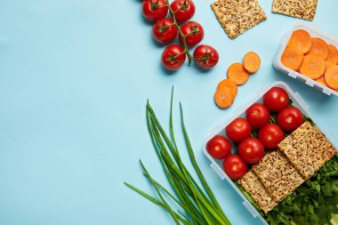 top view of arrangement of food containers with fresh healthy vegetables and cookies isolated on blue