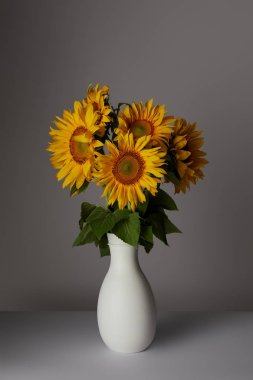 beautiful bouquet of yellow sunflowers in vase, on grey