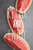Fotografie flat lay with watermelon pieces on grey concrete tabletop, with relax and enjoy lettering