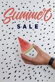 Fényképek levágott lövés ember görögdinnye darab tartja kezében a fehér felület a nyári eladó betűk