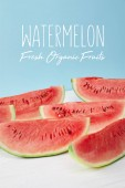 sweet watermelon slices on white surface on blue backdrop, with watermelon fresh organic fruits lettering